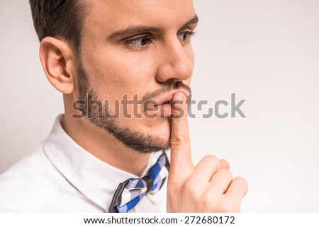 Keep silence! Handsome young man in white shirt is holding finger on lips while standing against grey background. - stock photo
