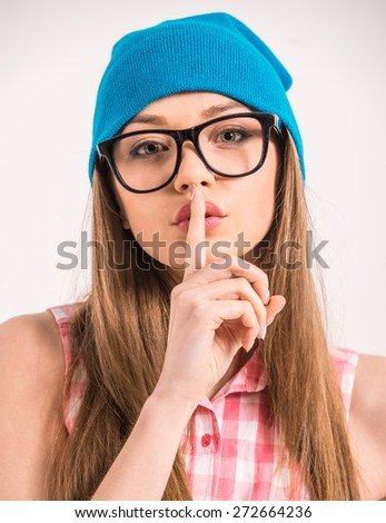 Keep silence! Stylish girl is holding finger on lips while standing against grey background. - stock photo