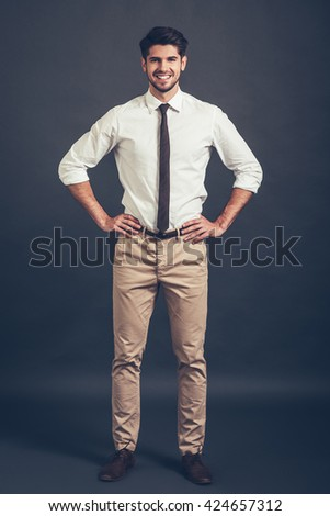 Keep smiling. Full length of confident young handsome man keeping arms akimbo and looking at camera with smile while standing against grey background - stock photo