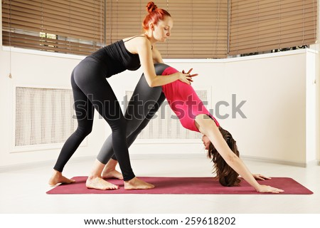 Keeping back straight with instructor assistance at bending yoga exercise - stock photo