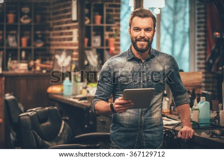 Keeping business on top with digital technologies. Cheerful young bearded man looking at camera and holding digital tablet while standing at barbershop - stock photo