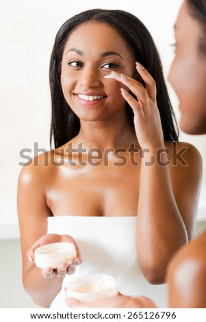 Keeping her skin fresh and smooth. Beautiful young African woman spreading cream on her face and smiling while standing against a mirror in bathroom  - stock photo