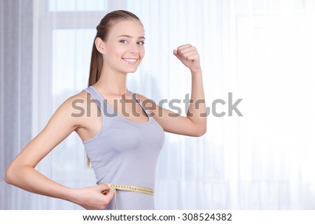 Keeping the diet. Delighted charming young girl holding her hand up and measuring the waist line while standing near window. - stock photo
