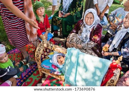 KEMIN, KYRGYZSTAN - AUGUST 2: Elderly village women tell the story of folk traditions of childbirth on August 2, 2013 in Kemin, Kyrgyzstan. Central Asian Kyrgyzstan has population near 5.4 million - stock photo