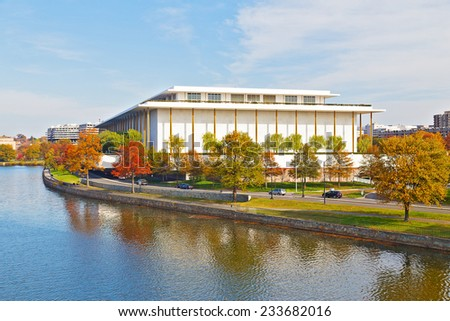 Kennedy Performing Arts Center in autumn, Washington DC. Modern building of Kennedy Center and colorful trees are reflected in Potomac River. - stock photo
