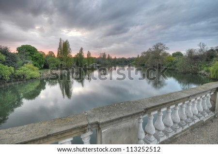 Kensington Gardens, once the private gardens of Kensington Palace, is one of the Royal Parks of London, lying immediately to the west of Hyde Park. A view over the water as the sun is setting. - stock photo