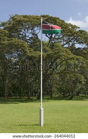 Kenya, flag waves in green grass yard of Karen Blixen Museum and Blixen home in Nairobi, Kenya, Africa - stock photo