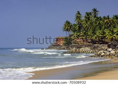Kerala beach, India with ocean's waves palms - stock photo