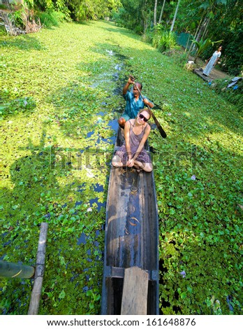KERALA, INDIA - APRIL 2013: Canoe at Alleppey backwaters with tourist  - stock photo