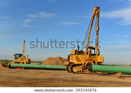 KERN COUNTY, CA - JUNE 27, 2015: Heavy equipment with pipelayer attachment is ready to handle pipe installation in the oil fields. Water and steam piping is used for secondary recovery techniques.