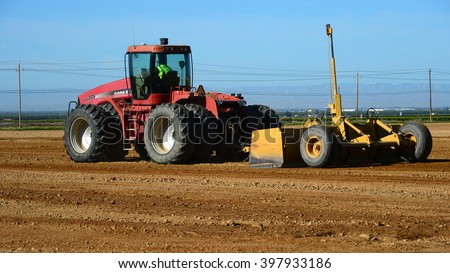 KERN COUNTY, CA - MARCH 28, 2016: Construction site preparation is accomplished with heavy equipment. The vertical mast contains a laser detector to aid in adhering to proper lines and grades. - stock photo