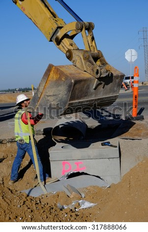 KERN COUNTY, CA - SEPTEMBER 17, 2015: Concrete sewer pipe is guided into place in trench by workman, suspended from the heavy equipment bucket.