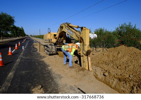 KERN COUNTY, CA - SEPTEMBER 17, 2015: The foreman on a sewer installation project closely inspects the trench made by a backhoe prior to burying the pipe.  - stock photo