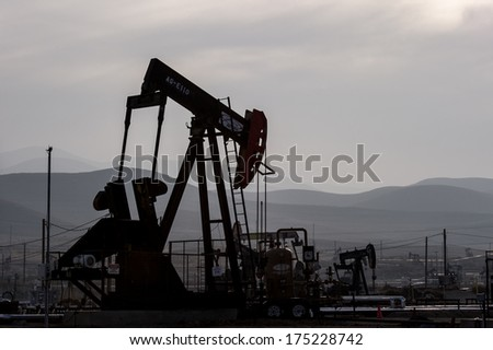 KERN COUNTY, CALIFORNIA - NOVEMBER 26, 2013: Pumpjacks extract oil from an oilfield in Kern County, CA. About 15 billion barrels of oil could be extracted using hydraulic fracturing in California. - stock photo