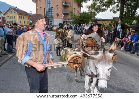 Kerns, Switzerland - 1 October 2016: people marching with farm animals at the annual rural transhumance parade of Kerns on the Swiss alps