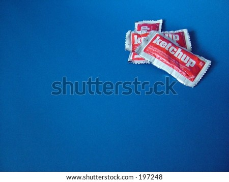 Ketchup packets on blue background - stock photo