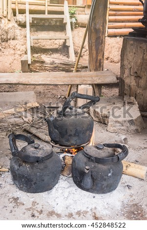 kettle boiling on stove in the kitchen tribal rural north of Thailand. - stock photo