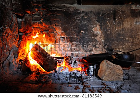 kettle in the old bricked fireplace indoors - preparing food - stock photo