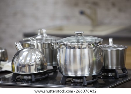 kettle, stainless steel pan on gas cooker - stock photo