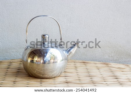 kettle still life on mat weave and concrete wall background