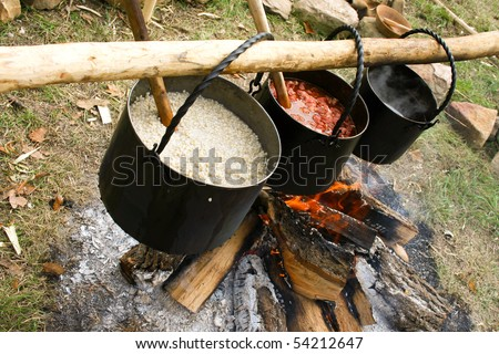 kettle with boiling soup over campfire in dusk - stock photo