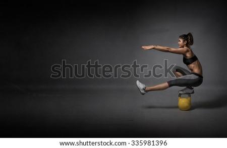 kettlebell balance demonstration, dark background - stock photo