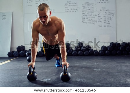Kettlebell push-up exercise - athletic man doing functional workout at the gym