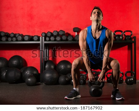 Kettlebell swing workout training man at gym with red walls - stock photo