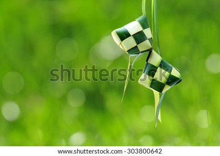 Ketupat or rice dumpling is a local delicacy during the festive season.  Ketupat, a natural rice casing made from young coconut leaves for cooking rice on a bokeh or blur background - stock photo