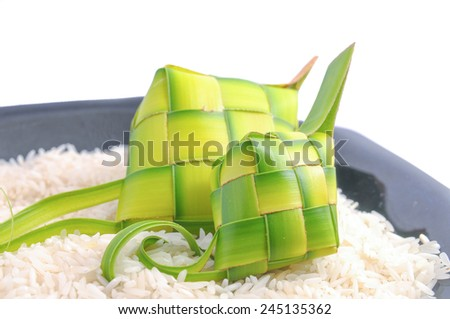Ketupats, a natural rice casing made from young coconut leaves for cooking rice on rice grain and black glass plate  - stock photo