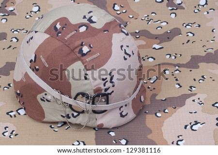 kevlar helmet with dog tags on desert camouflage cover - stock photo