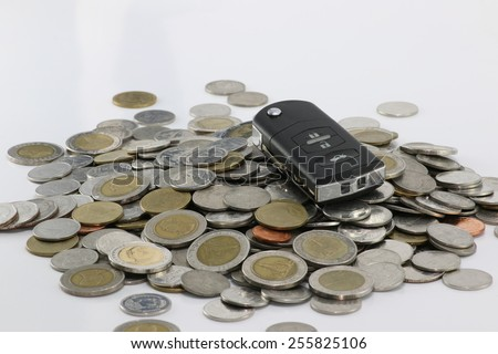 key a car on a pile of coins. how much money to have a car. - stock photo