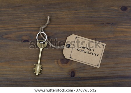 Key and a note on a wooden table with text - Protect Your Identity - stock photo