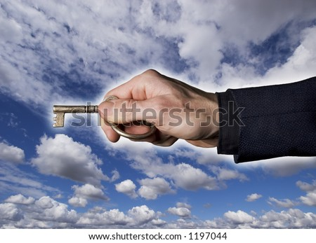 Key and hand against a dark, turbulent sky. - stock photo