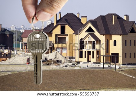 key in fingers on a background cottages - stock photo