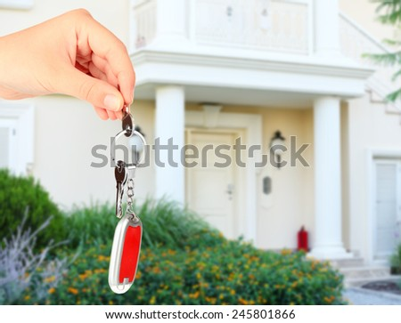 Key in hand on house background, Real estate concept - stock photo