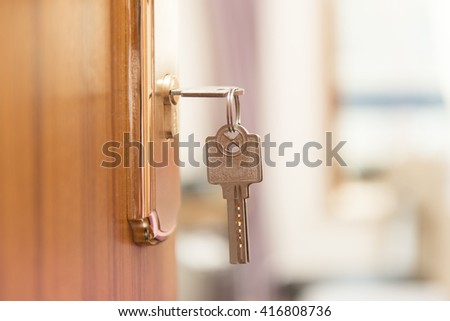 Key in keyhole on door - stock photo