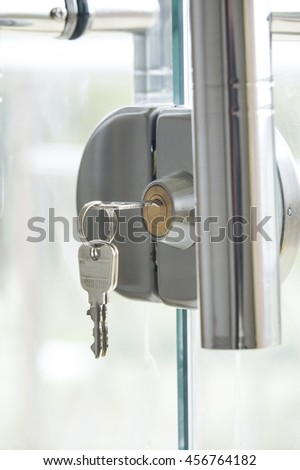 Key in keyhole on glass door - stock photo