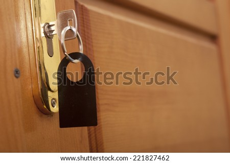 key in keyhole with blank label  - stock photo