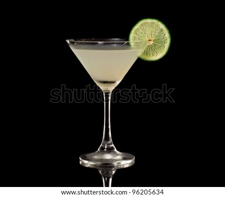 Key lime martini isolated on a black background garnished with a lime wheel - stock photo
