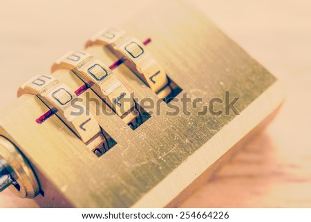 Key pad lock on wooden background process vintage style picture - stock photo