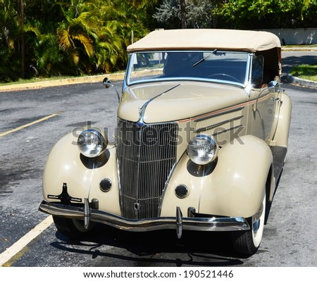 KEY WEST, FL-APRIL 27: A beige 1936 Ford Touring Phaeton Convertible Sedan automobile,  quartering frontal view from above, in parking lot in Key West, Florida on April 27, 2014. - stock photo
