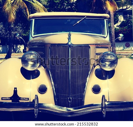 KEY WEST, FL-APRIL 27: Closeup frontal view of a beige 1936 Ford Touring Phaeton Convertible Sedan in Key West, Florida on April 27, 2014, with instagram-type filter applied for vintage effect. - stock photo