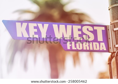 Key West Florida Street Sign. A street sign marking Key West, Florida. Backed by a palm tree with a sunset flare. - stock photo