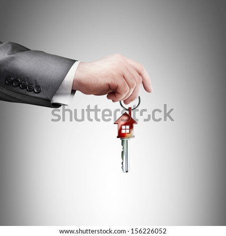 Key with red home shape in hand. High resolution  - stock photo