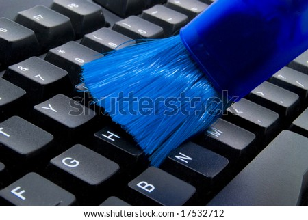 Keyboard Cleaner in blue color cleaning a keyboard in black color - stock photo