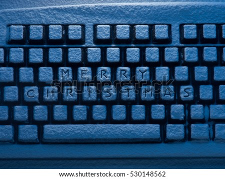 keyboard covered with snow with words Merry Christmas on keys illuminated with blue light