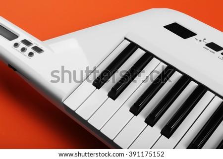 Keyboard of synthesizer on orange background - stock photo