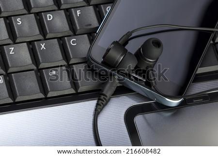 keyboard, smartphone, earphones on an office desk - stock photo