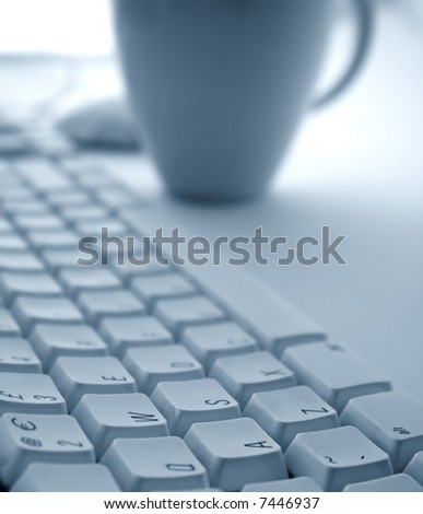 Keyboard with Coffee Cup with narrow Depth of Filed - stock photo